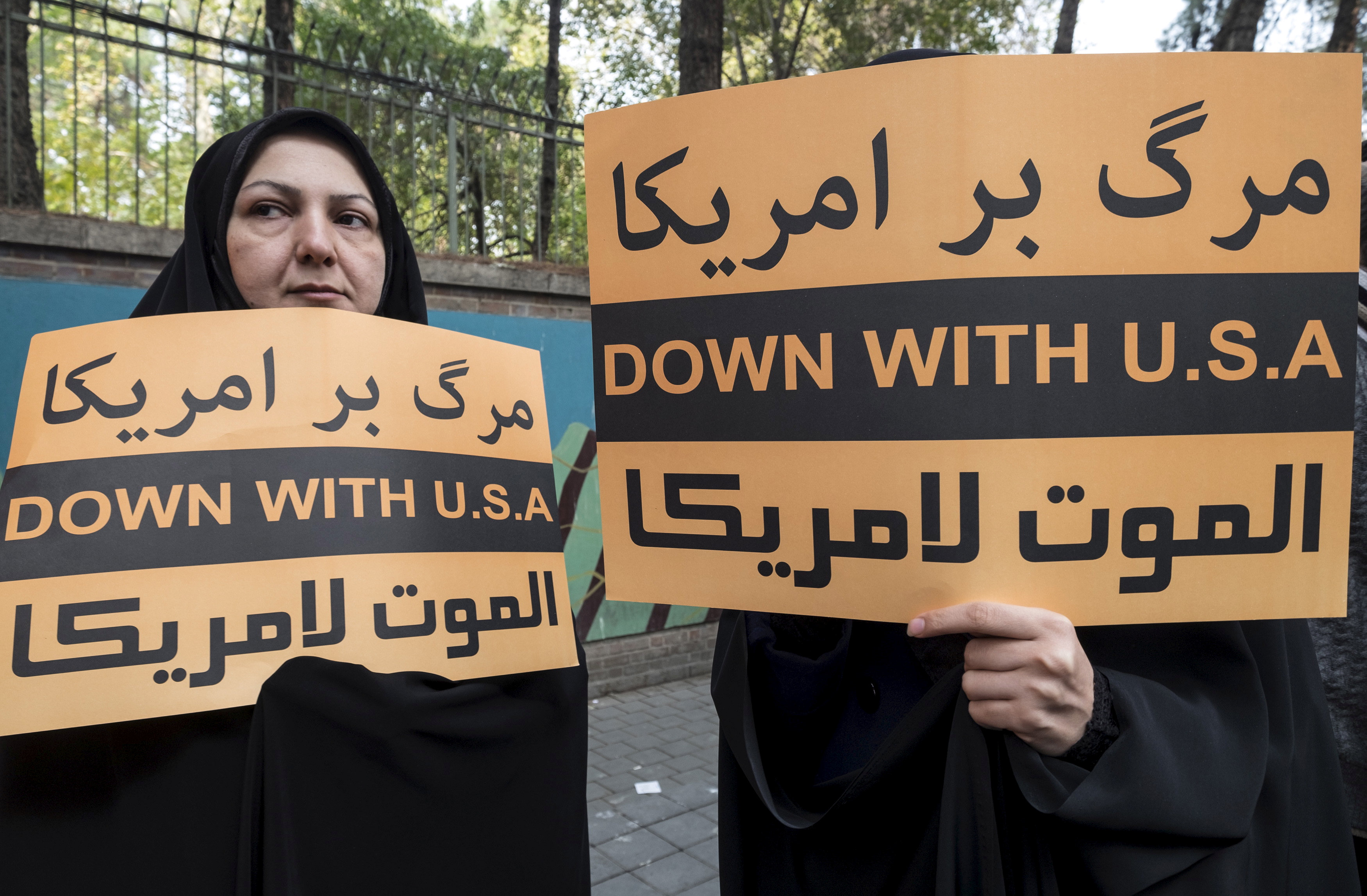 FILE PHOTO: Women hold anti-U.S. banners during a demonstration outside the former U.S. embassy in Tehran November 4, 2015. REUTERS/Raheb Homavandi/TIMA/File Photo