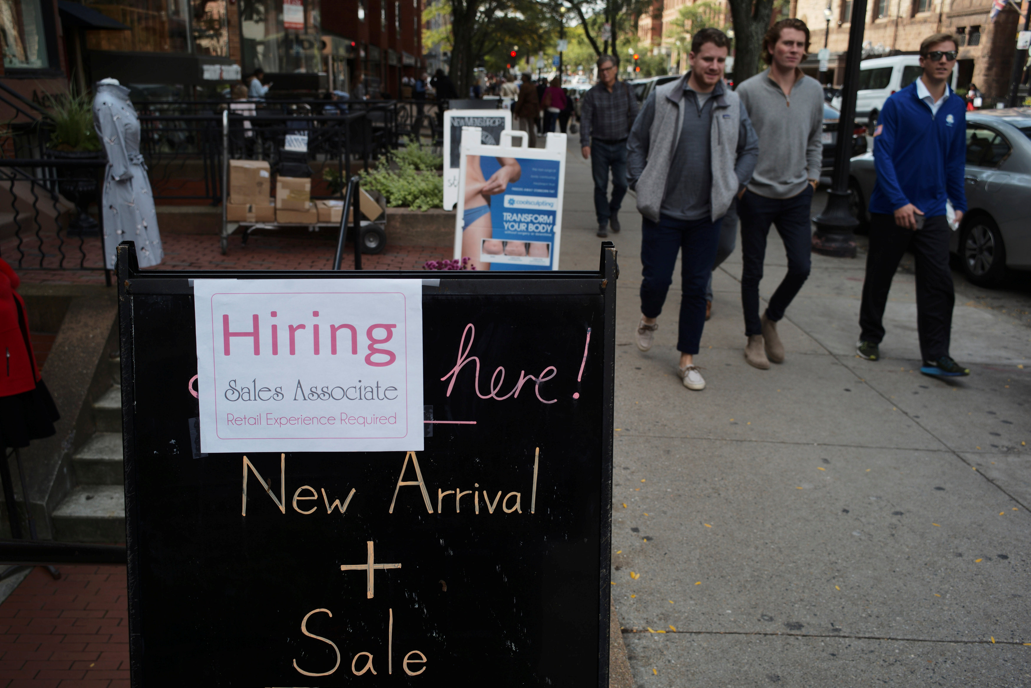 Pedestrians pass a sign advertising a sale and a job opening at a shop on Newbury Street in Boston, Massachusetts, U.S., October 11, 2017. REUTERS/Brian Snyder