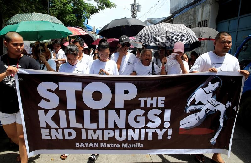 FILE PHOTO: Relatives and loved ones of Leover Miranda, 39, a drug-related killings victim, hold a streamer calling to stop the continuing rise of killings due to the President Rodrigo Duterte's ruthless war on drugs, during a funeral march at the north cemetery in metro Manila, Philippines August 20, 2017. REUTERS/Romeo Ranoco