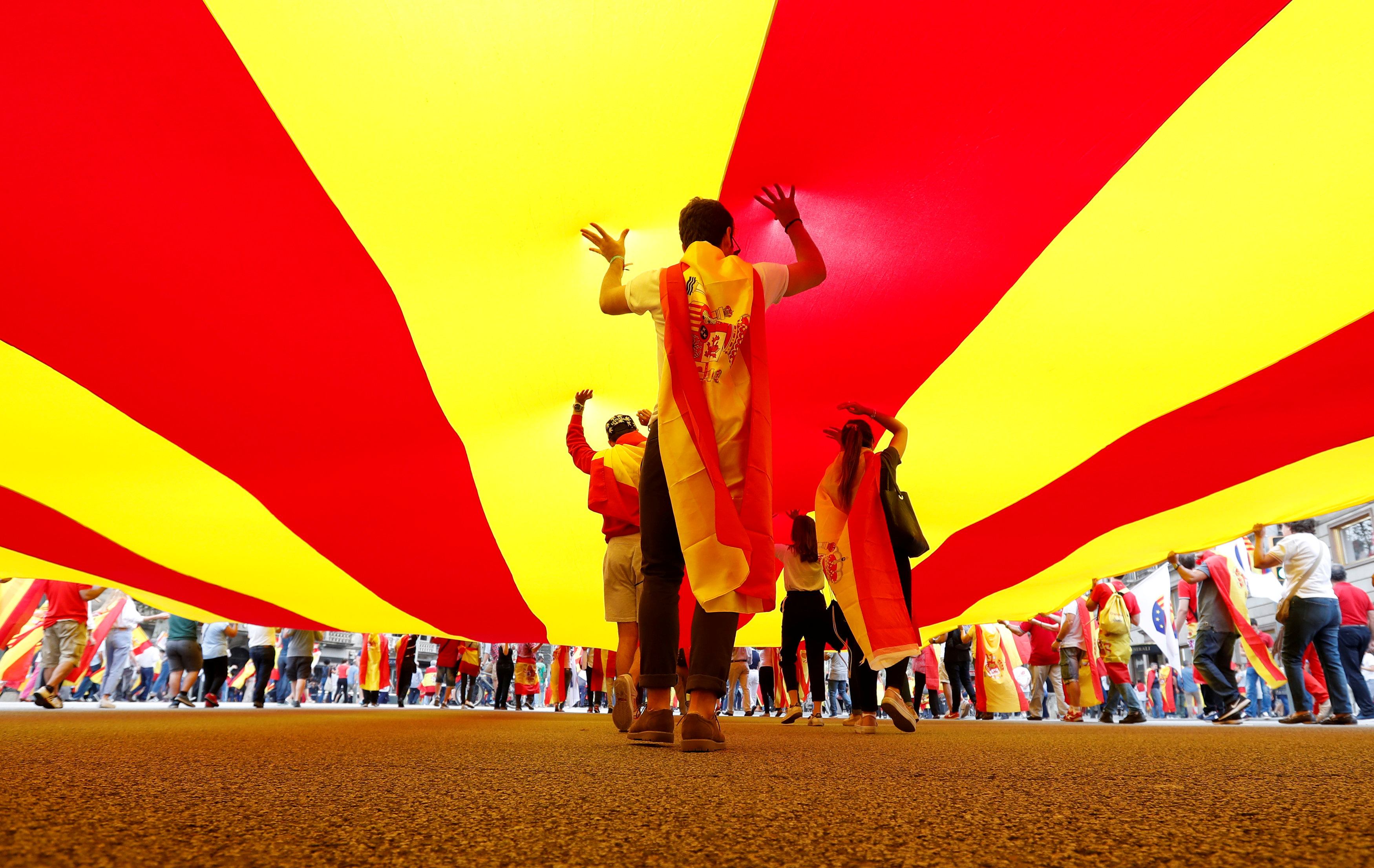 People walk under a huge Catalan flag during Spain's National Day in Barcelona. REUTERS/Gonzalo Fuentes
