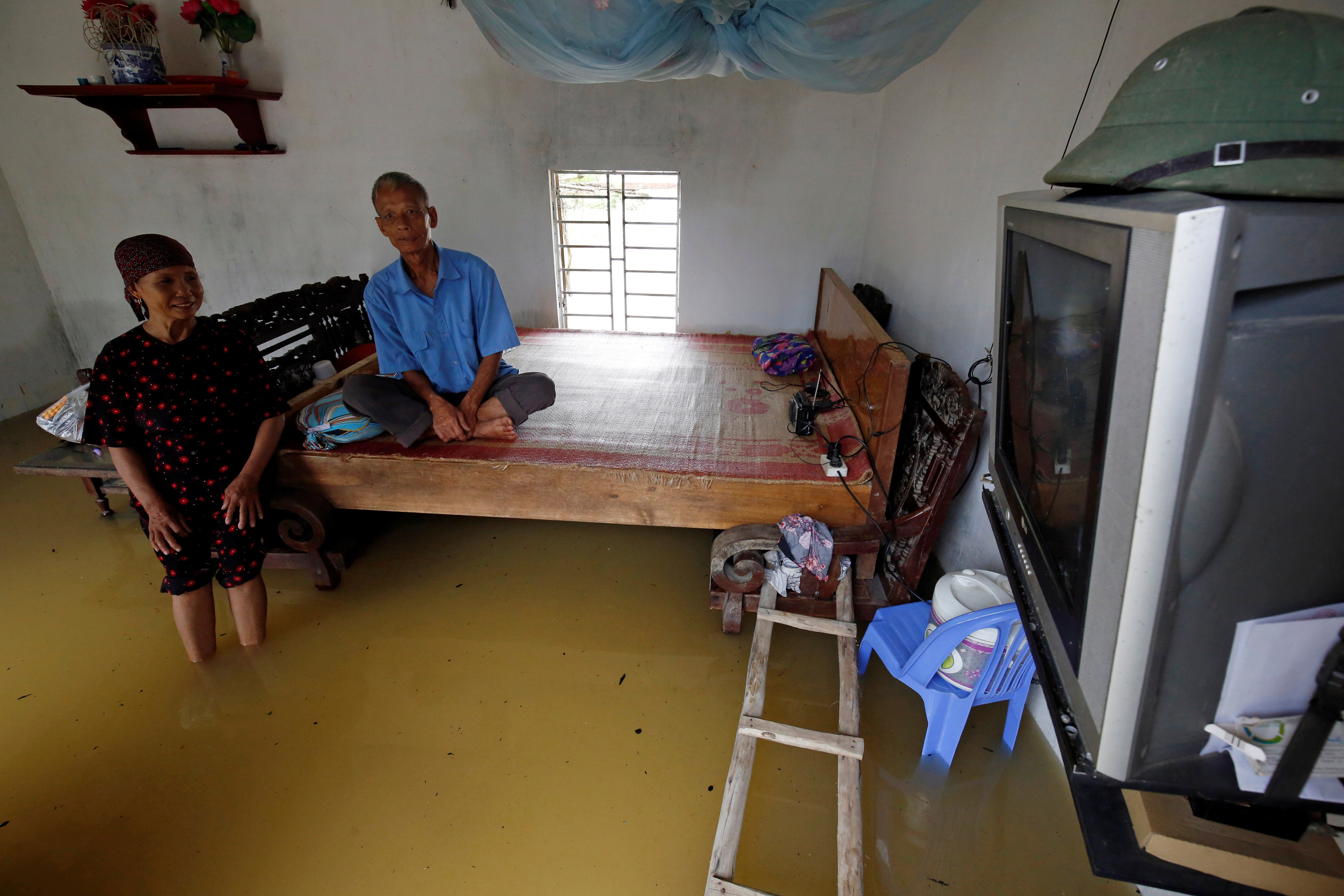 A couple watches TV in their flooded house after a tropical depression in Hanoi, Vietnam October 13, 2017. REUTERS/Kham