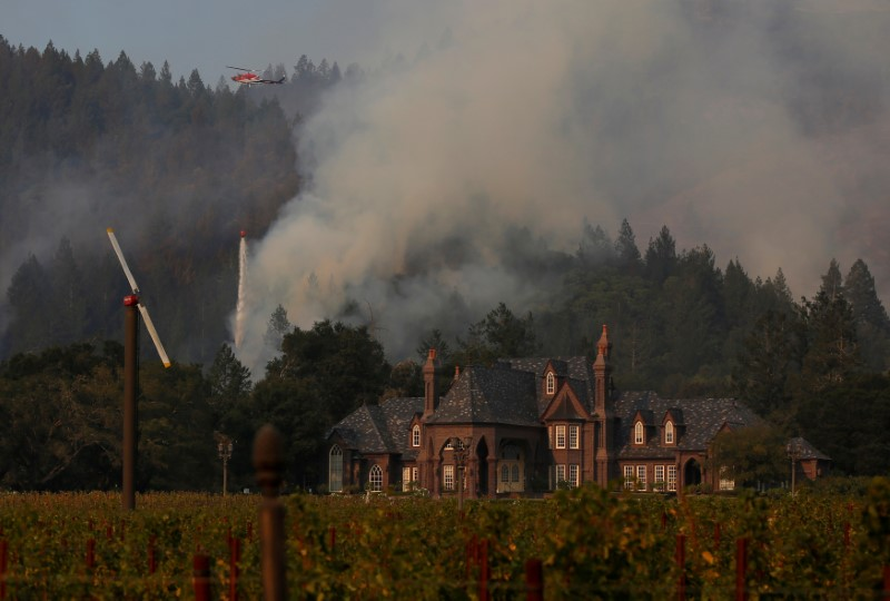 A firefighting helicopter drops water to defend a vineyard from an approaching wildfire in Santa Rosa.