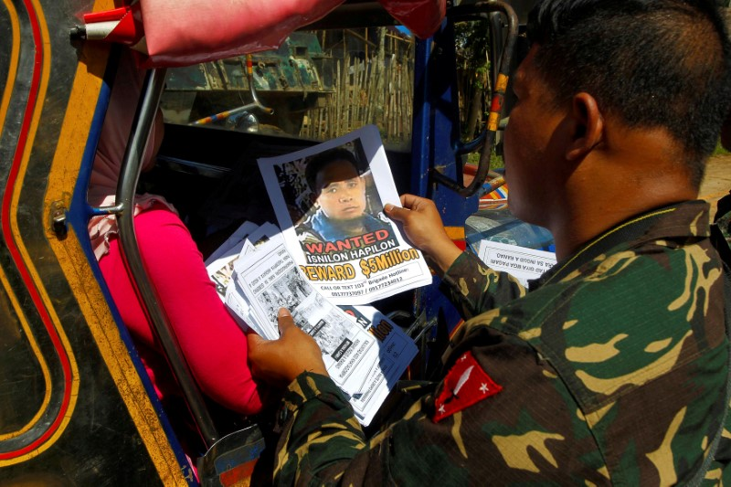 Soldiers distribute pictures of a member of extremist group Abu Sayyaf Isnilon Hapilon, who has a U.S. government bounty of $5 million for his capture, in Butig, Lanao del Sur in southern Philippines February 1, 2017.