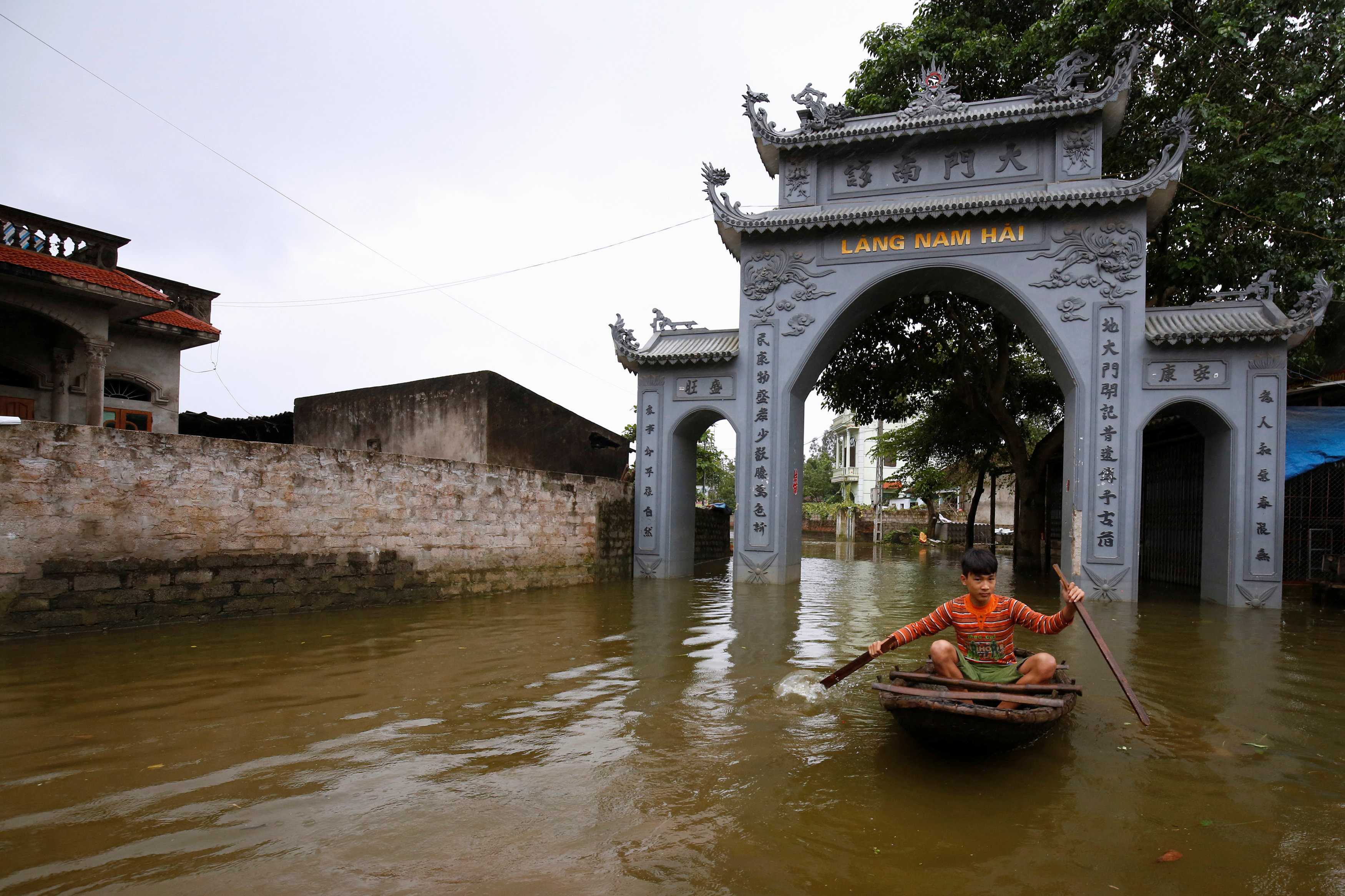A boy paddles a boat past a flooded village's gate after a heavy rain caused by a tropical depression in Hanoi, Vietnam October 16, 2017.