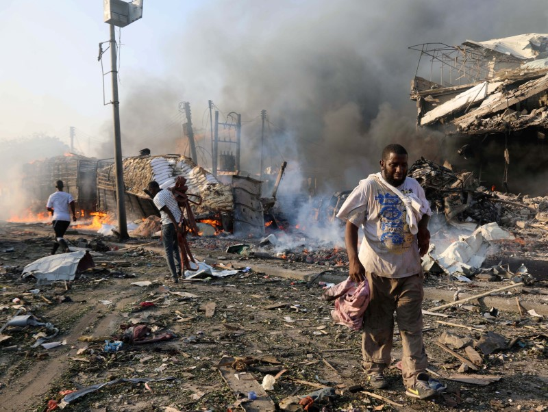 Civilians walk at the scene of an explosion in KM4 street in the Hodan district of Mogadishu. REUTERS/Feisal Omar