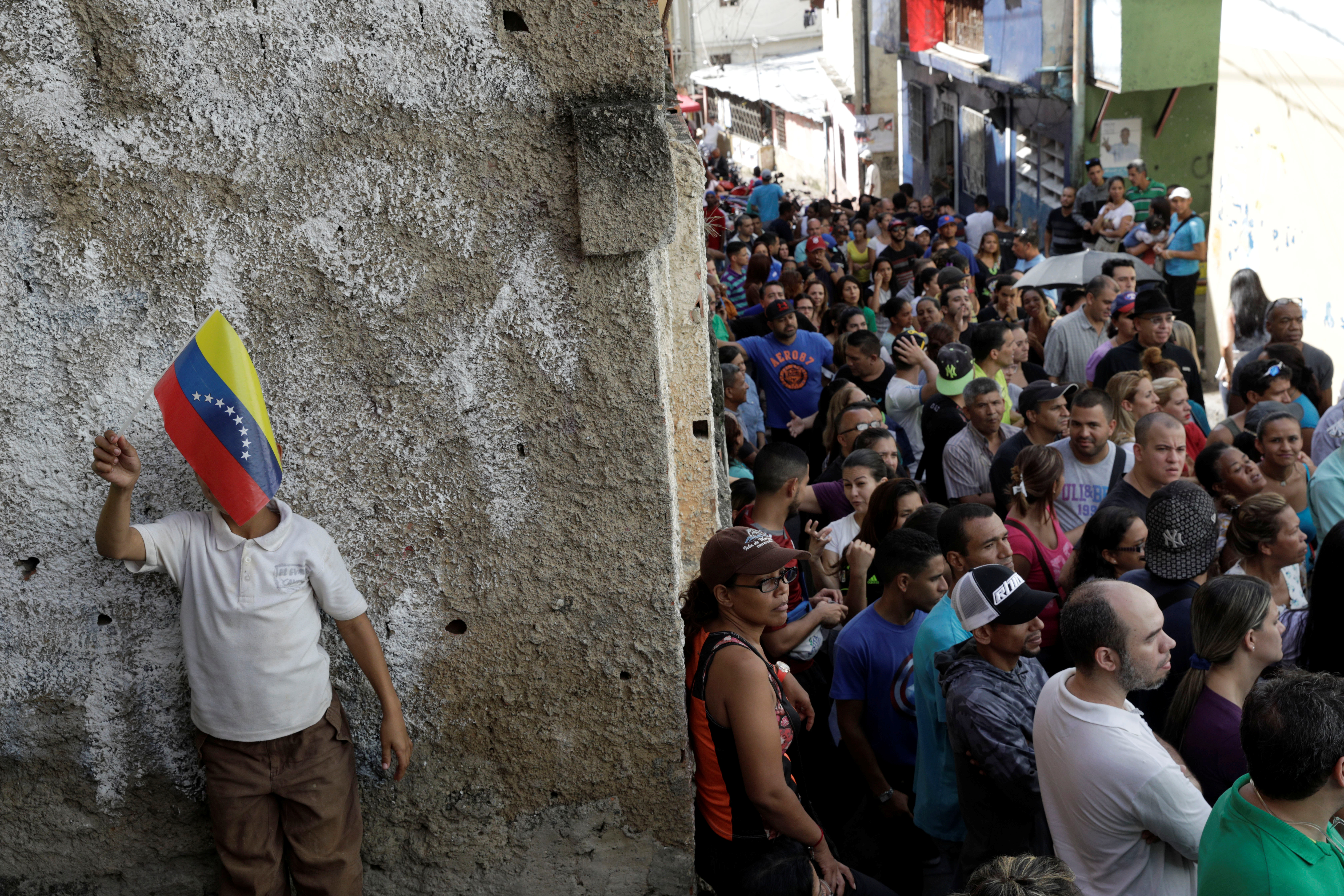 Venezuelan citizens wait in line at a polling station during a nationwide election for new governors in Caracas, Venezuela. REUTERS/Ricardo Moraes