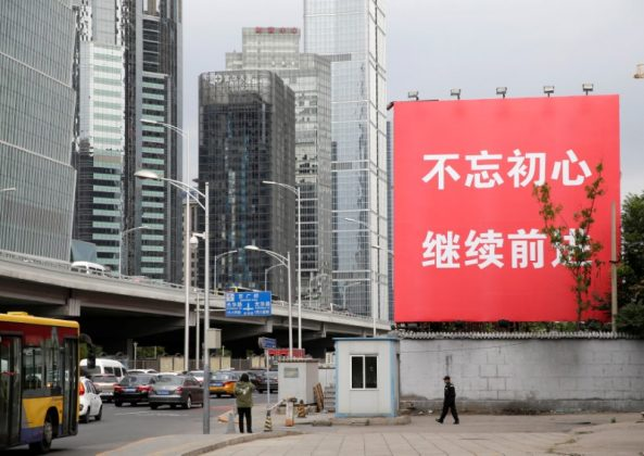 """A security guard walks under a banner reading """"Stay true to the mission, continue to move foward"""" in Beijing's central business area, as the capital prepares for the 19th National Congress of the Communist Party of China, October 14, 2017. REUTERS/Jason Lee"""