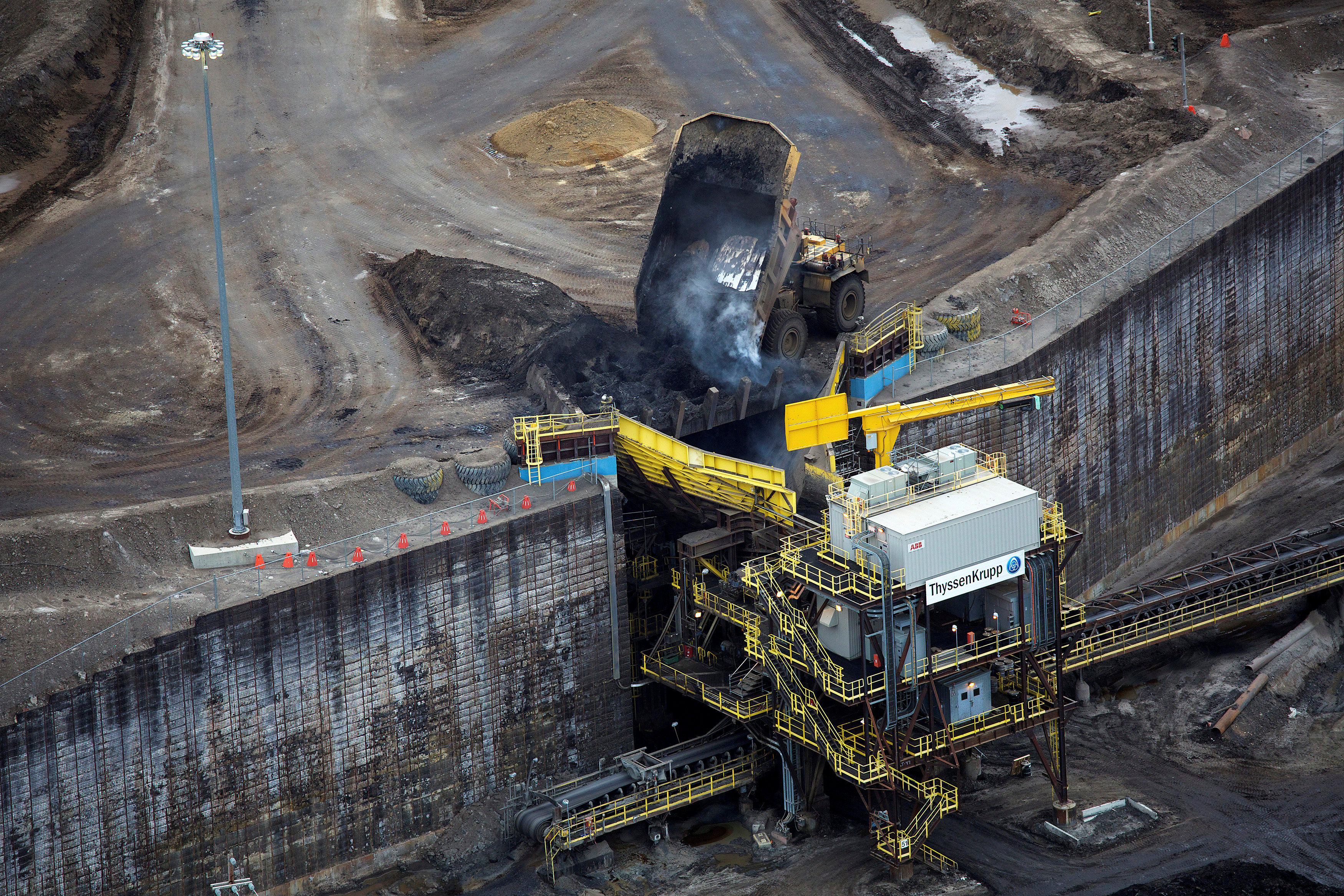 FILE PHOTO - Giant dump trucks dump raw tar sands for processing at the Suncor tar sands mining operations near Fort McMurray, Alberta, Canada on September 17, 2014. REUTERS/Todd Korol/File Photo
