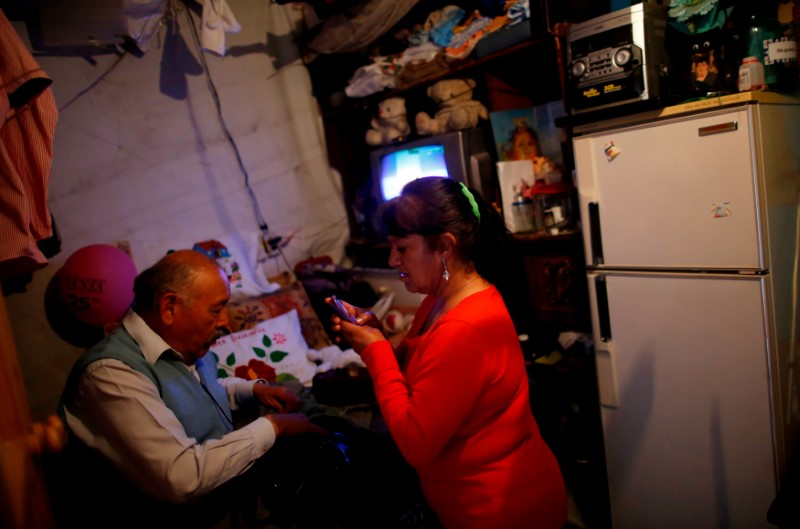 Maria de Lourdes Rosales, 64, who lost her home in the 1985 earthquake, answers her phone in her house at the camp known as No.3 in Mexico City, Mexico, October 16, 2017. The camp was founded in 1985 after an earthquake, which killed around 5,000 people. REUTERS/Carlos Jasso
