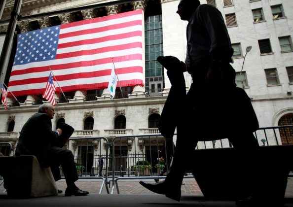 Morning commuters are seen outside the New York Stock Exchange, July 30, 2012.