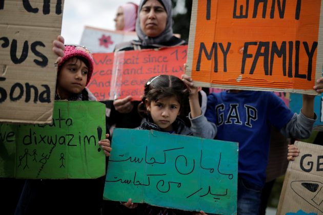 """A girl holds a placard reading, """"where is my Mother, where is my Father"""", as refugees protest, some announcing a hunger strike, as they seek reunification with family members in Germany, near the parliament building in Athens, Greece, November 1, 2017."""
