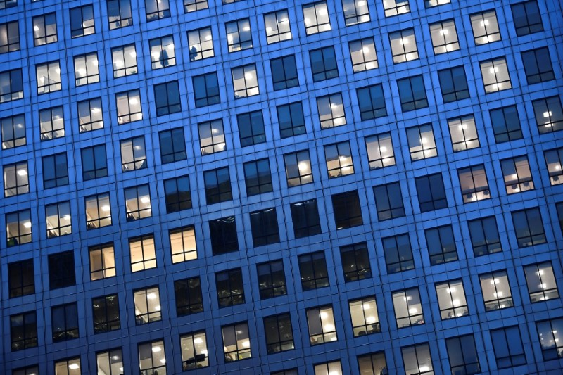 Office lights are on at dusk in the Canary Wharf financial district, London, Britain,