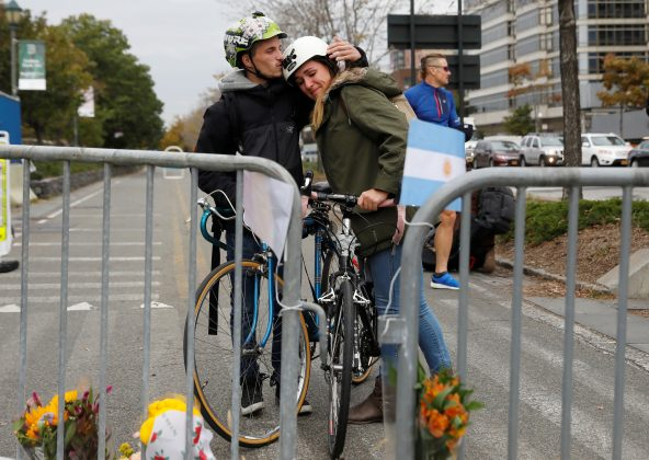 Amaya Lopez-Silvero, 20, and Elliot Levy, 21, embrace by a makeshift memorial for victims of Tuesday's attack lay outside a police barricade on the bike path next to West Street a day after a man driving a rented pickup truck mowed down pedestrians and cyclists on a bike path alongside the Hudson River in New York City, New York, U.S.