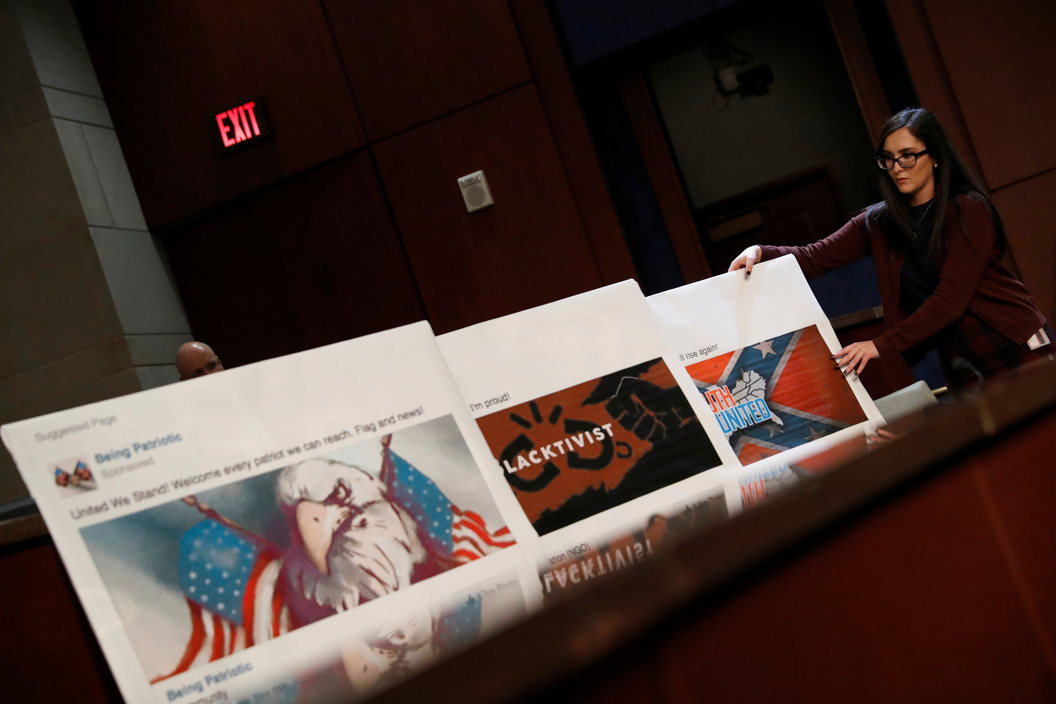 An aide puts out examples of Facebook pages, as executives appear before the House Intelligence Committee to answer questions related to Russian use of social media to influence U.S. elections, on Capitol Hill in Washington, U.S., November 1, 2017.