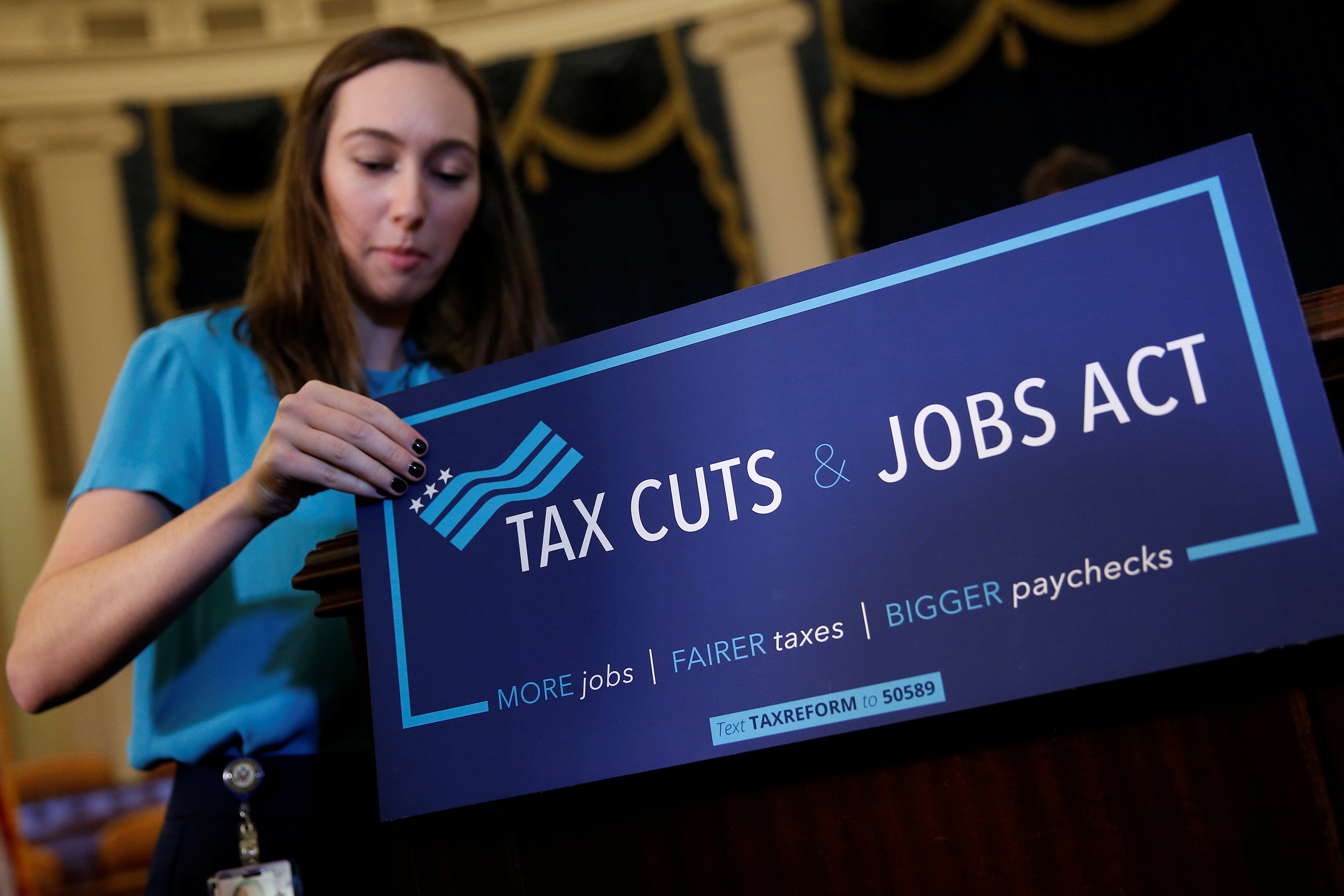 A congressional aide places a placard on a podium for the House Republican's legislation to overhaul the tax code on Capitol Hill.