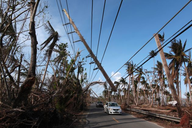 Cars drive under a partially collapsed utility pole, after the island was hit by Hurricane Maria in September, in Naguabo, Puerto Rico