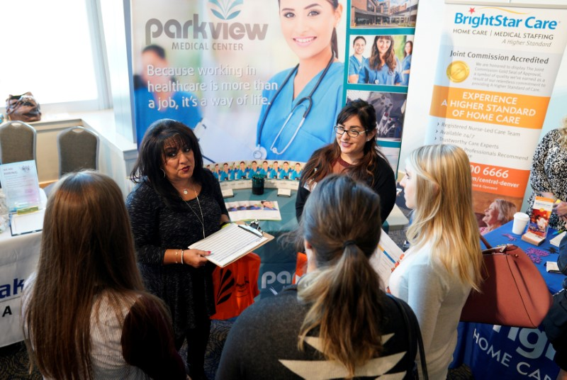 FILE PHOTO: Job seekers listen to a recruiter at the Colorado Hospital Association job fair in Denver, Colorado, U.S. on October 4, 2017