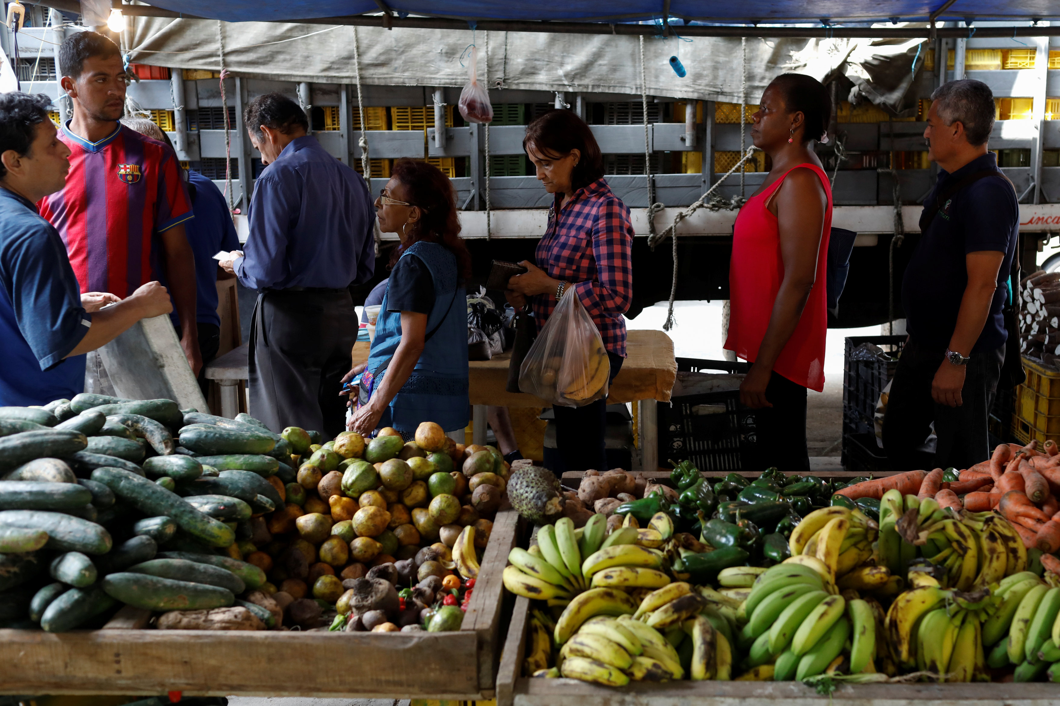 People line up to pay for their fruits and vegetables at a street market in Caracas, Venezuela November 3, 2017.