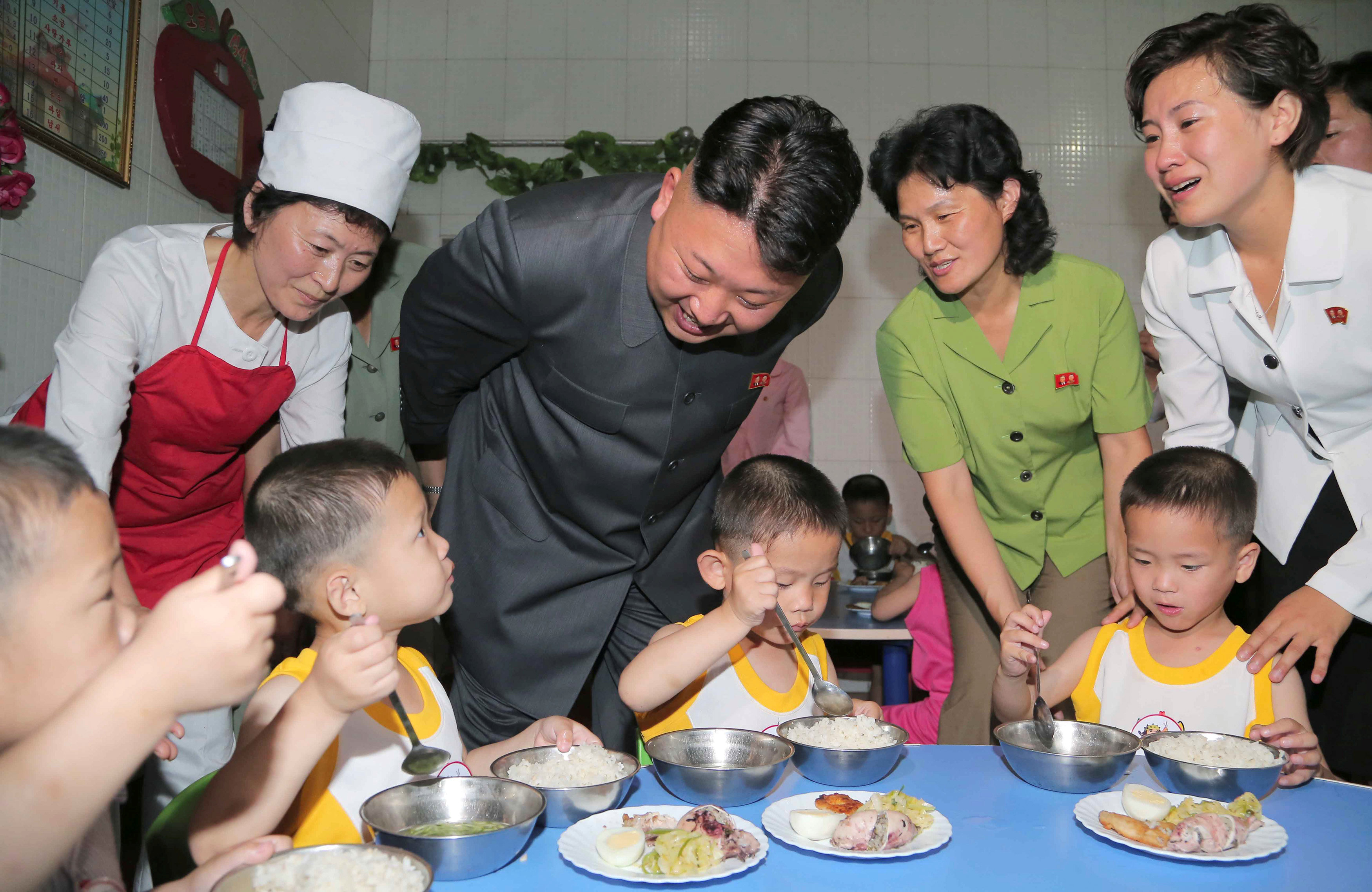 North Korean leader Kim Jong Un smiles as children eat during his visit to the Pyongyang Orphanage on International Children's Day in this undated photo released by North Korea's Korean Central News Agency (KCNA) in Pyongyang