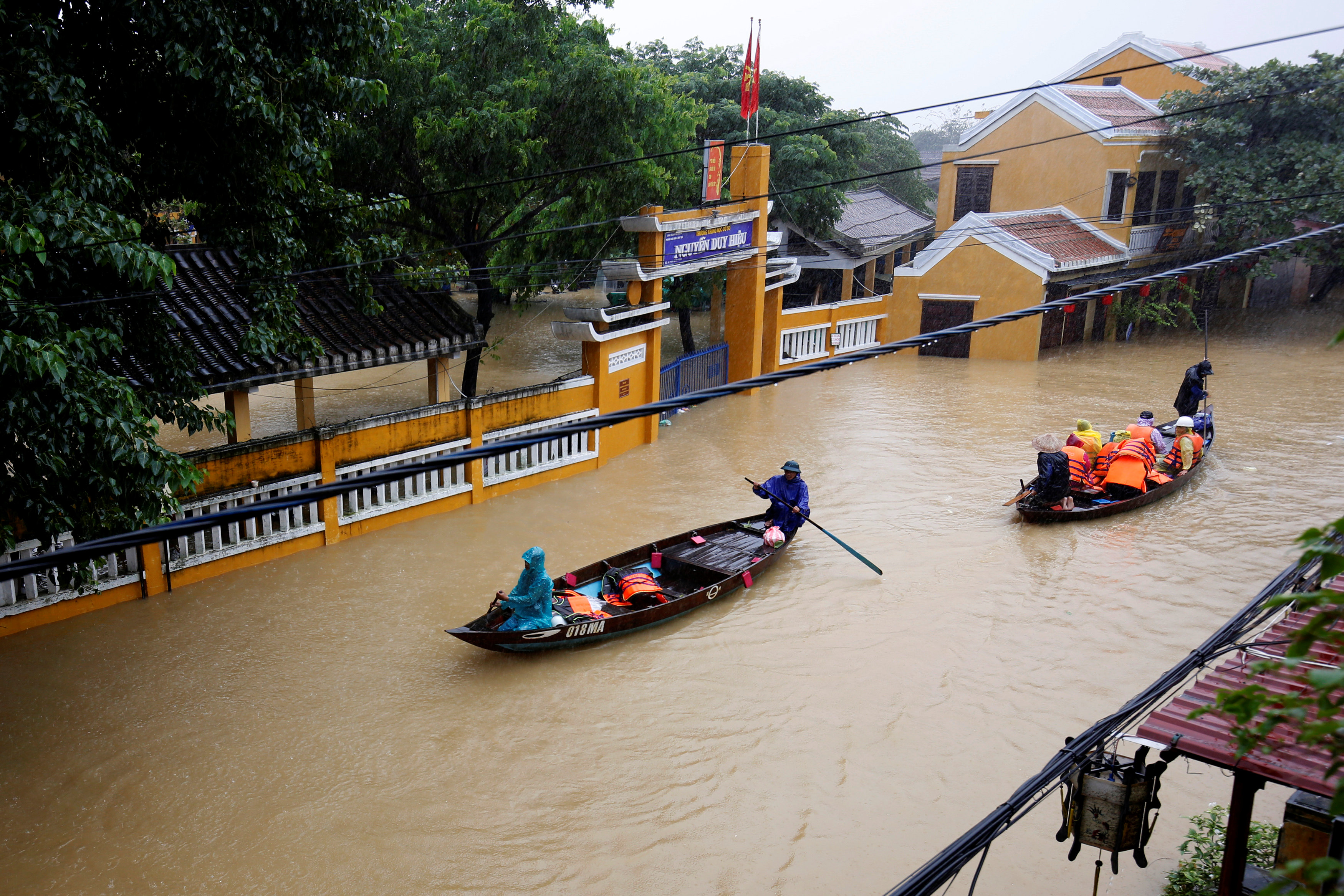 People ride a boat along submerged houses in UNESCO heritage ancient town of Hoi An after typhoon Damrey hits Vietnam November 6, 2017.