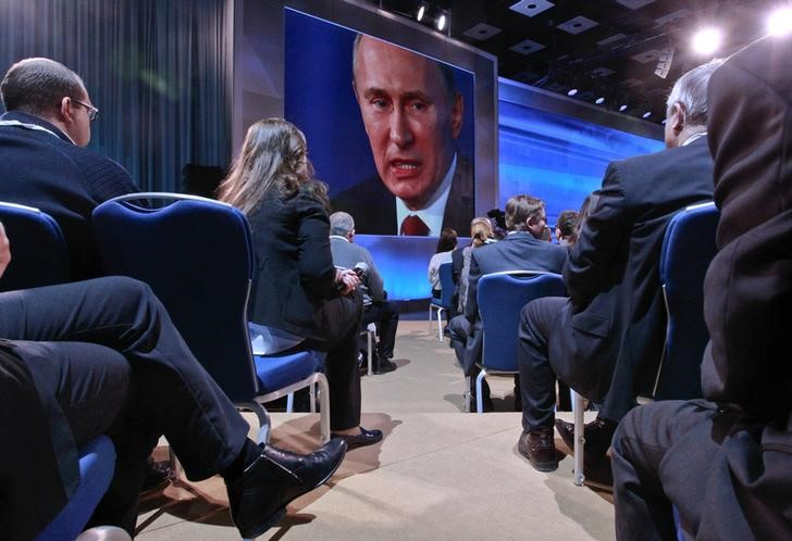 Journalists watch Russia's President Vladimir Putin on a big screen during his annual news conference in Moscow, December 20, 2012.