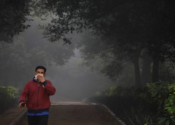 A man covers his face with a handkerchief as he walks ina park on a smoggy morning in New Delhi, India, November 9, 2017.