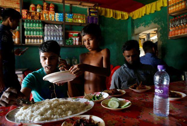 Azimul Hasan, 10, a Rohingya refugee boy, serves plates at a roadside hotel where he works at Jamtoli, close to Palong Khali camp, near Cox's Bazar, Bangladesh, November 12, 2017.