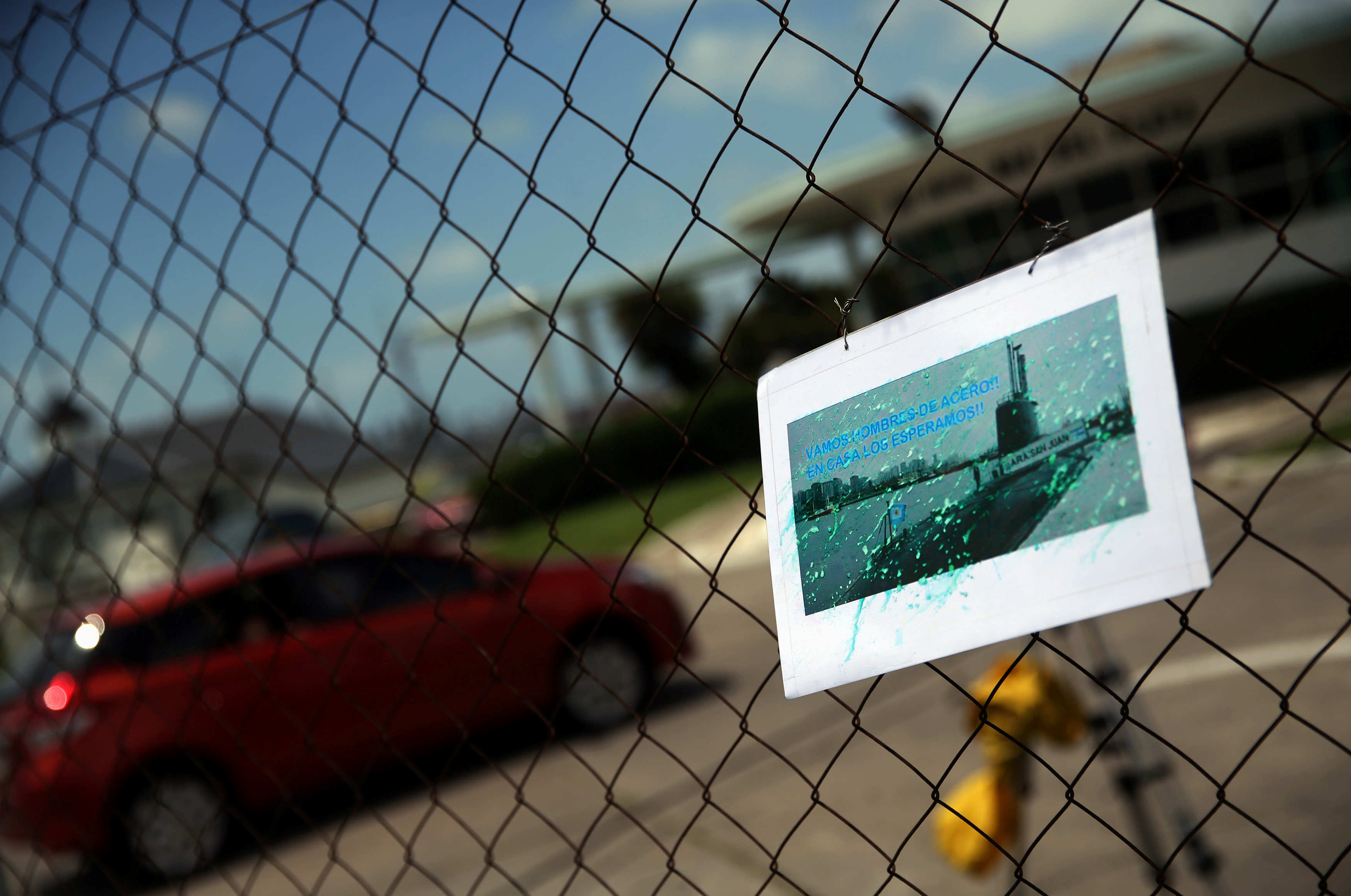 A car enters the Argentine Naval Base where the missing at sea ARA San Juan submarine sailed from as a picture of it hangs on a fence in Mar del Plata, Argentina November 19, 2017.