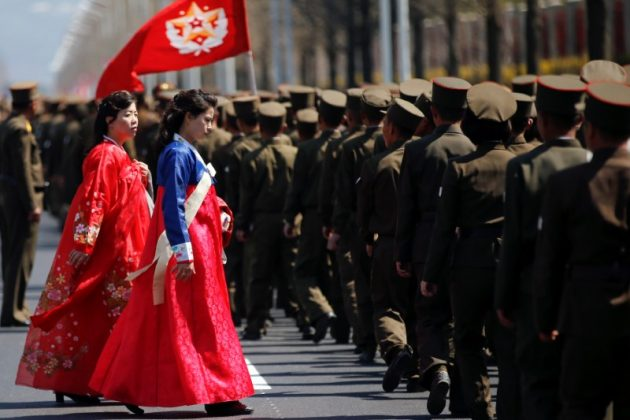 Women wearing traditional clothes walk past North Korean soldiers after an opening ceremony for a newly constructed residential complex in Ryomyong street in Pyongyang, North Korea April 13, 2017.