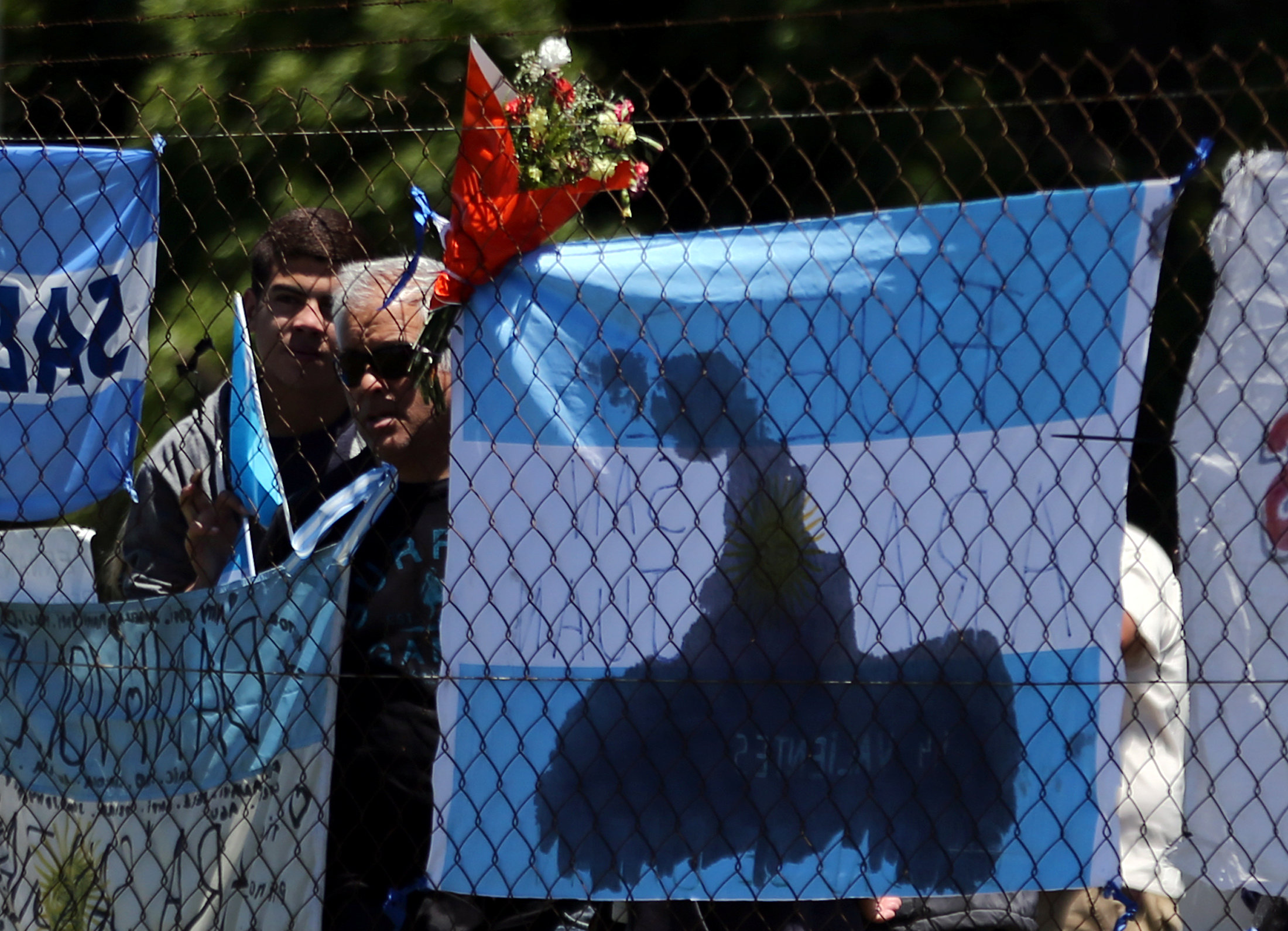 People stand next to a bouquet of flowers and banners in support of the 44 crew members of the missing at sea ARA San Juan submarine, outside an Argentine naval base in Mar del Plata, Argentina November 25, 2017.