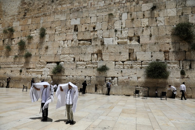 Youth hold their prayer shawls as they stand in front of the Western Wall, Judaism's holiest prayers site in Jerusalem's Old City May 17, 2017.