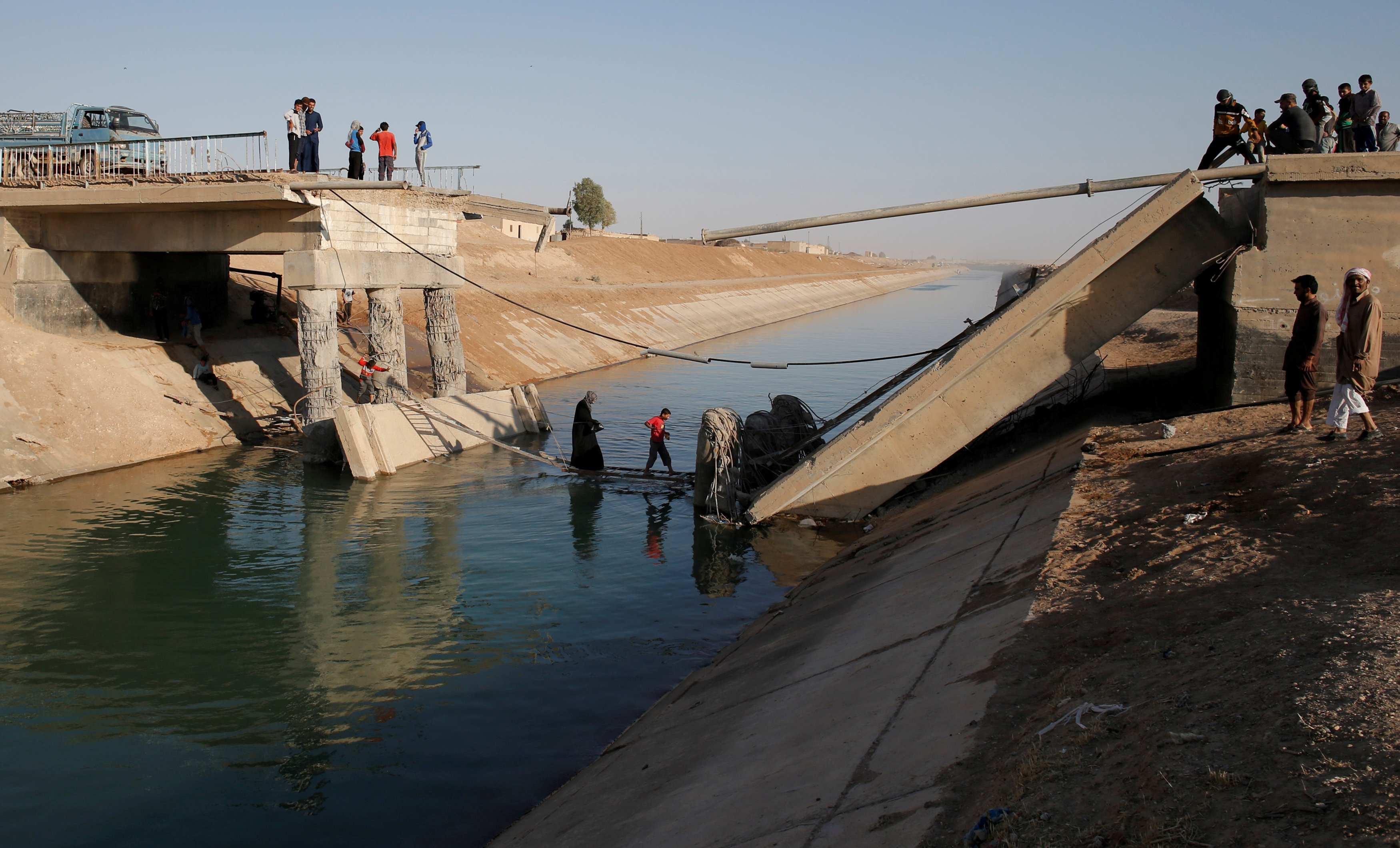 People cross a makeshift ladder in a village near Raqqa after a bridge was destroyed in fighting between the U.S.-led coalition and Islamic State, in Raqqa, Syria, June 16, 2017.