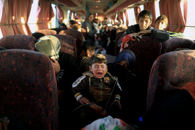 A boy who just fled a village controlled by Islamic State fighters cries as he sits with his family on a bus before heading to the camp at Hammam Ali south of Mosul, Iraq, February 22, 2017.