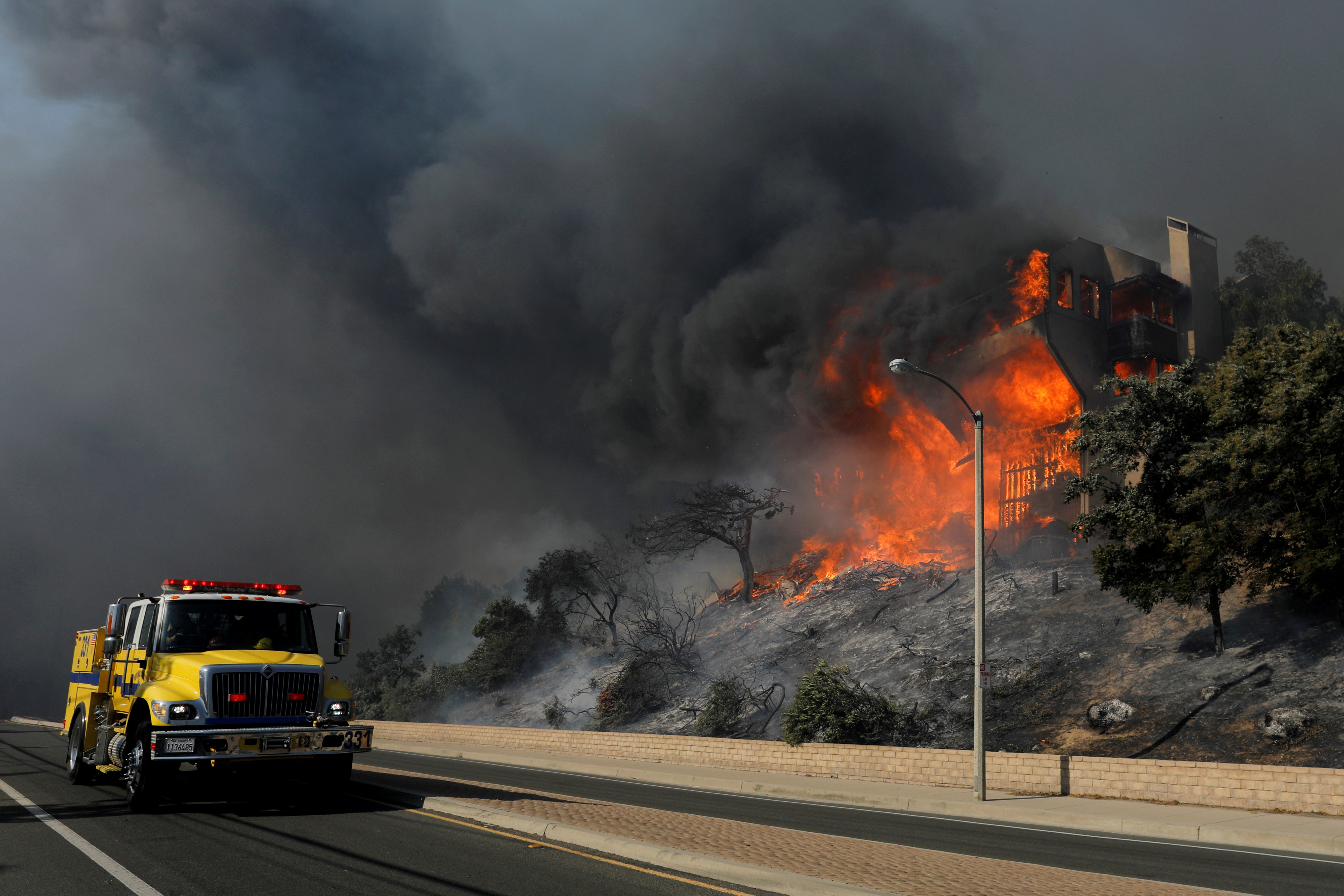 A fire crew passes a burning home during a wind-driven wildfire in Ventura.