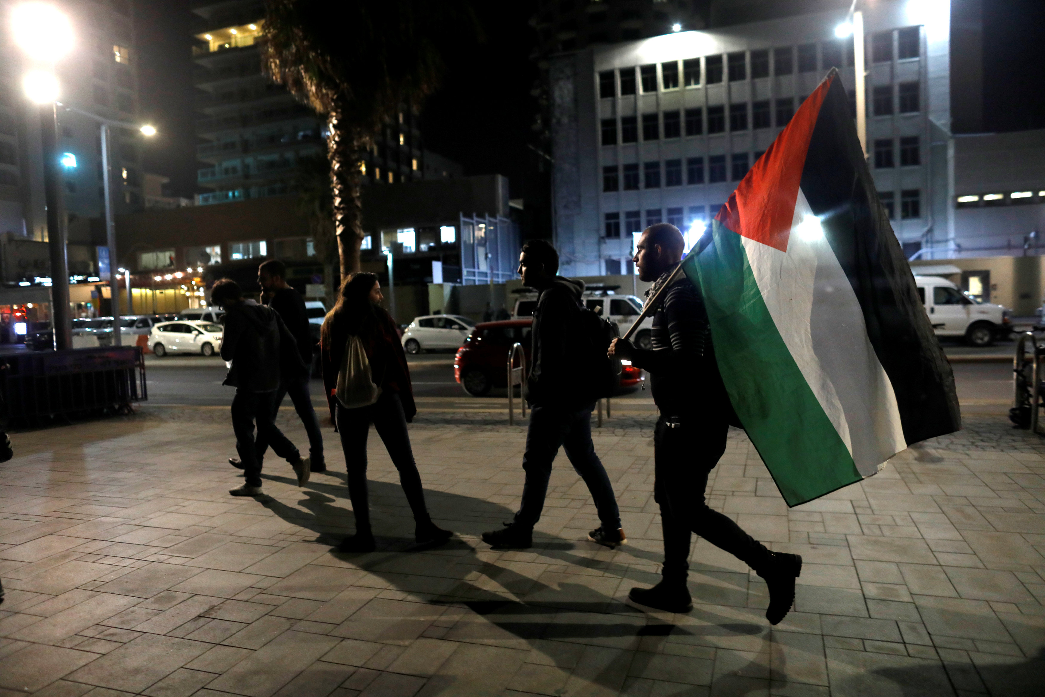 A protester carries a Palestinian flag at the end of a demonstration against U.S. President Donald Trump's decision to recognise Jerusalem as Israel's capital opposite to the American embassy in Tel Aviv, Israel December 12, 2017.