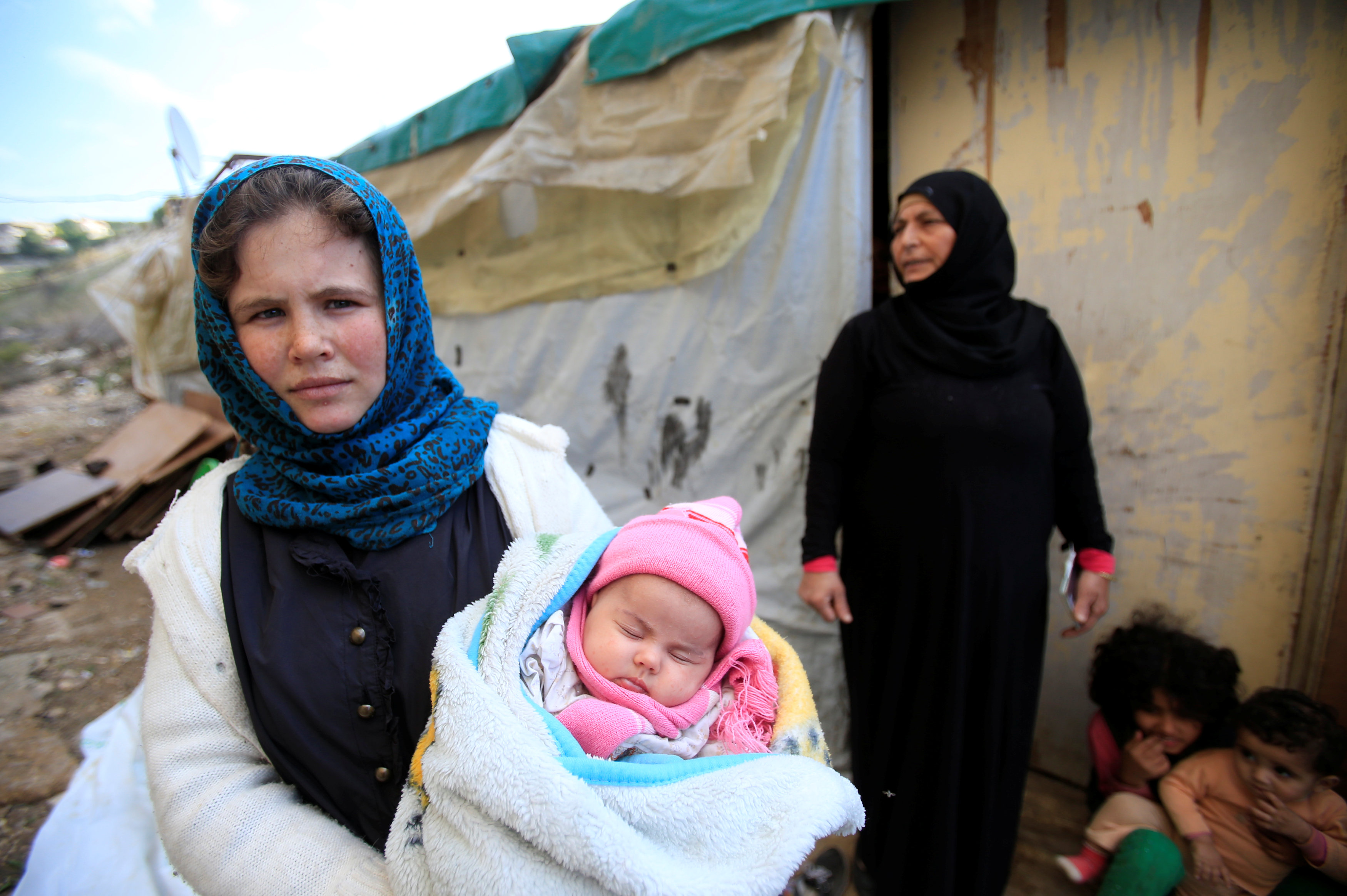 A Syrian refugee woman holds a child in Ain Baal village, near Tyre in southern Lebanon, November 27, 2017. Picture taken November 27, 2017.