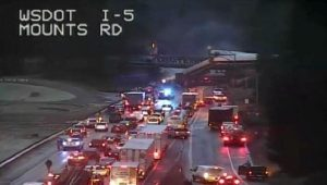 An Amtrak passenger train is seen derailed on a bridge over interstate highway I-5