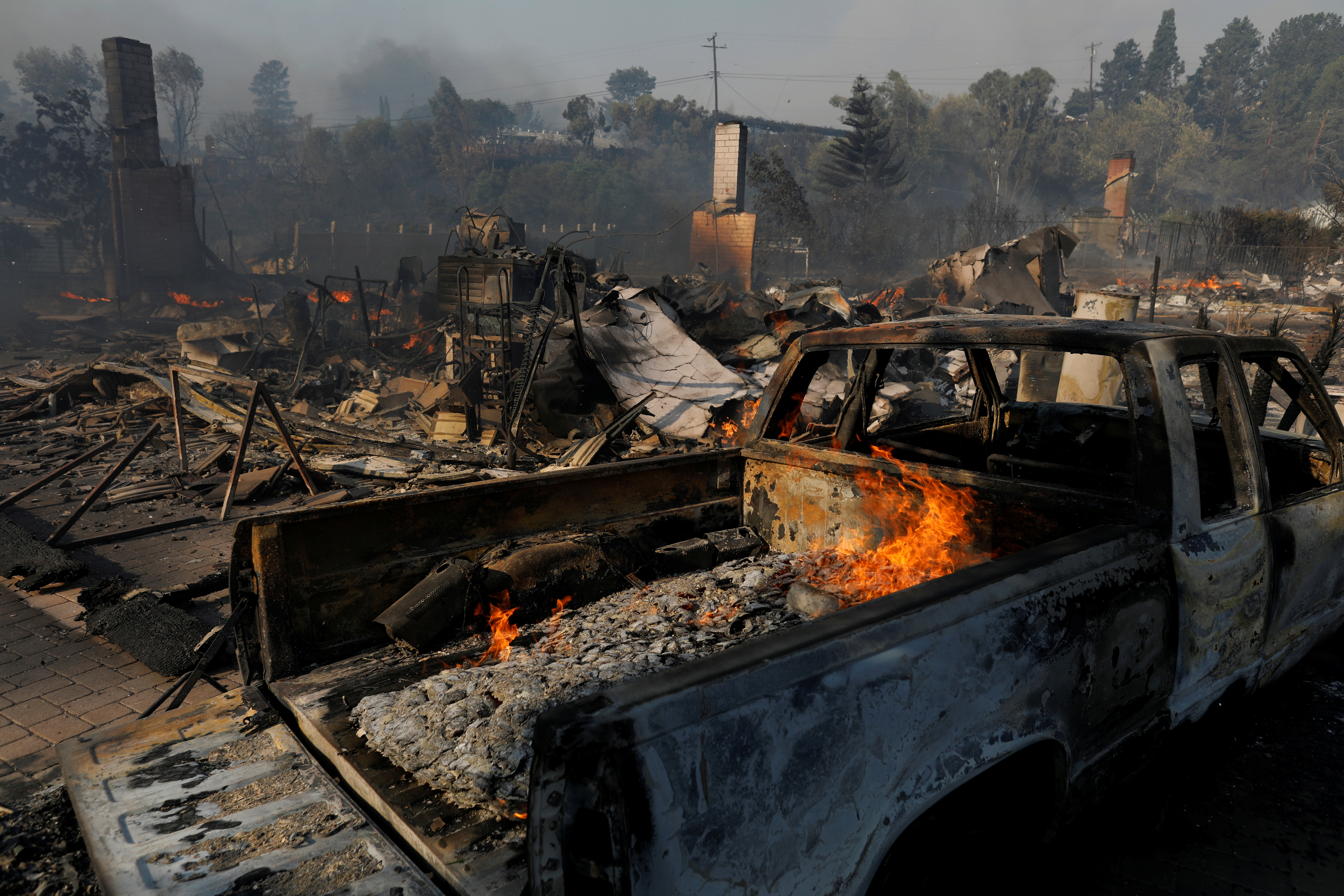 A home's remains are seen, next to a burnt out truck, after they were destroyed, during a wind-driven wildfire in Ventura.