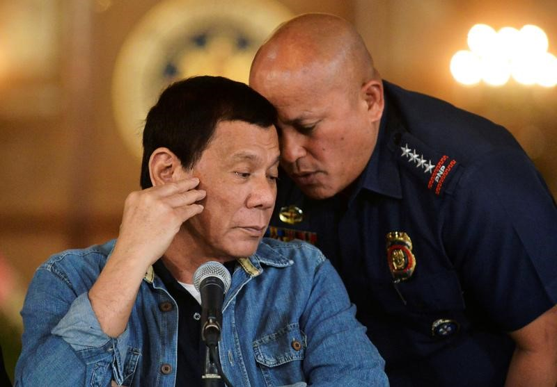 FILE PHOTO: Philippine National Police chief General Ronald Dela Rosa whispers to President Rodrigo Duterte during the announcement of the disbandment of police operations against illegal drugs at the Malacanang palace in Manila, Philippines