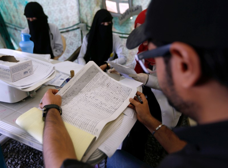 A health worker reviews a list of patients admitted to a cholera treatment center in Sanaa, Yemen