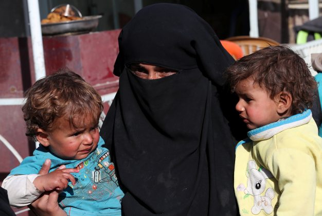 A Syrian woman and her children wait for food aid in front of an humanitarian aid distrubition center in Syrian border town of Jarablus, Syria, December 13, 2017.