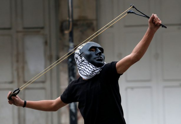 "A Palestinian demonstrator uses a slingshot to hurl stones towards Israeli troops during clashes at a protest as Palestinians call for a ""Day of Rage"" in response to U.S. President Donald Trump's recognition of Jerusalem as Israel's capital, in the West Bank city of Hebron December 22, 2017."