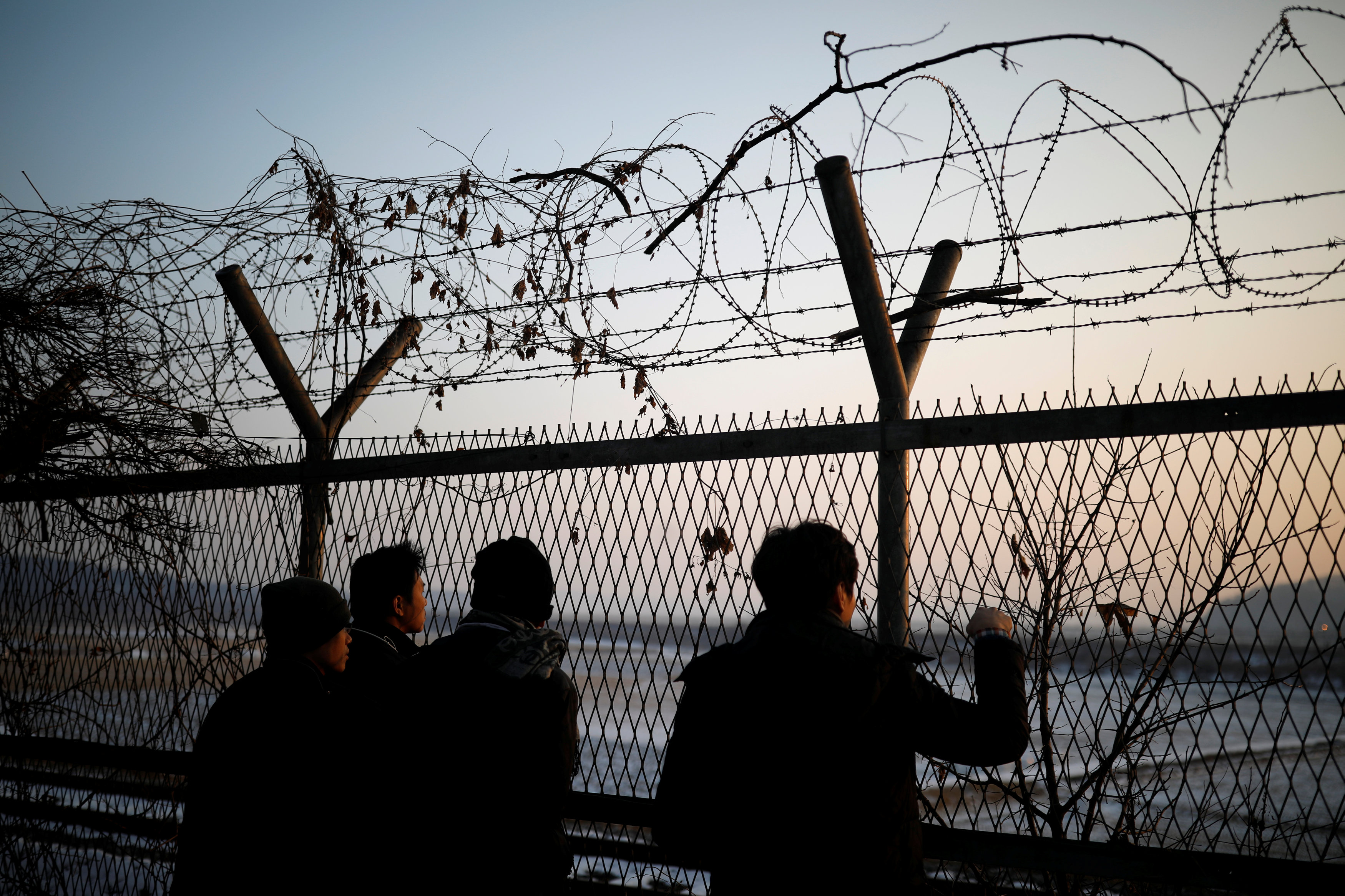 People look toward the north through a barbed-wire fence near the militarized zone separating the two Koreas, in Paju, South Korea, December 21, 2017.