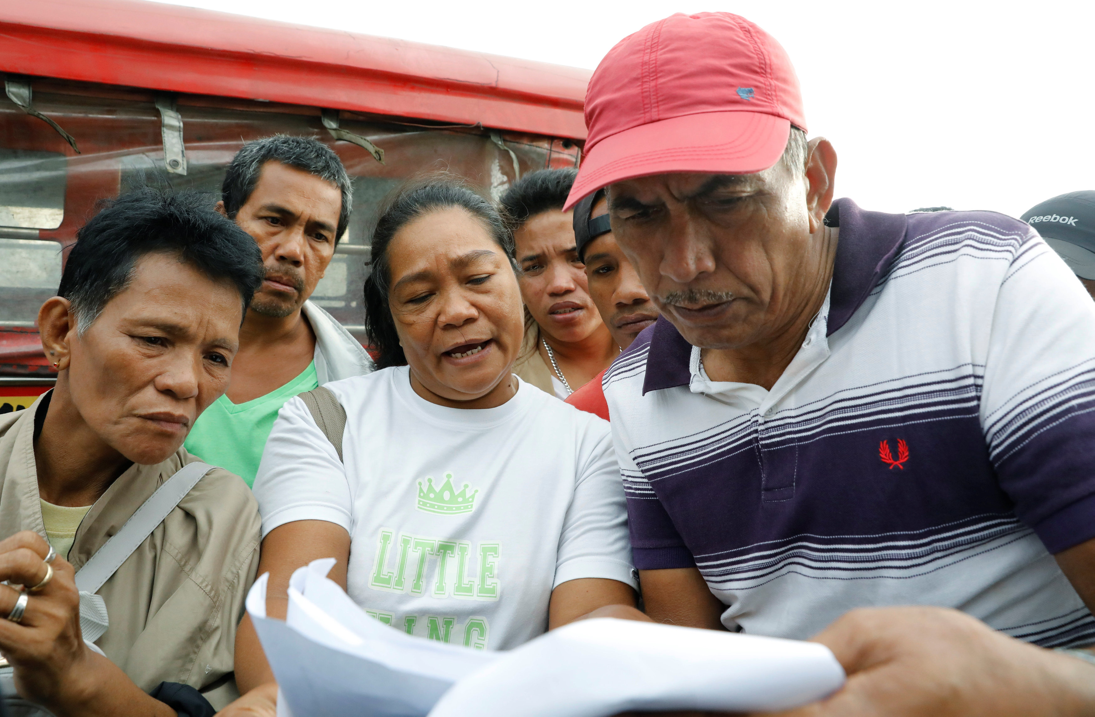 Filipinos look for their missing relatives on a list of survivors after a Philippine vessel capsized because of bad weather in Real, Quezon in the Philippines, December 22, 2017.