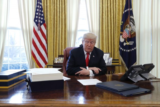 U.S. President Donald Trump sits at his desk before signing tax overhaul legislation in the Oval Office of the White House in Washington, U.S., December 22, 2017.