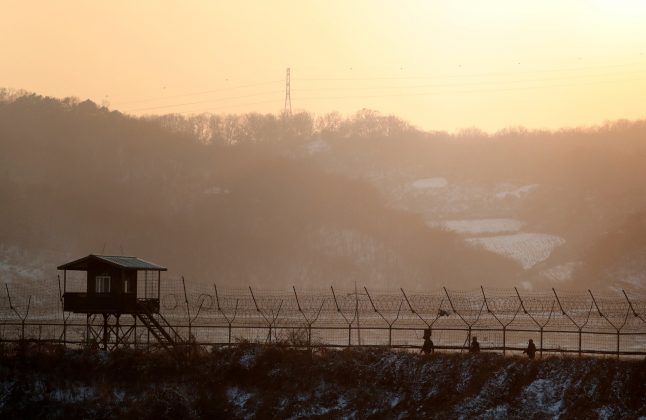 South Korean soldiers patrol along a barbed-wire fence near the militarized zone separating the two Koreas, in Paju, South Korea, December 21, 2017