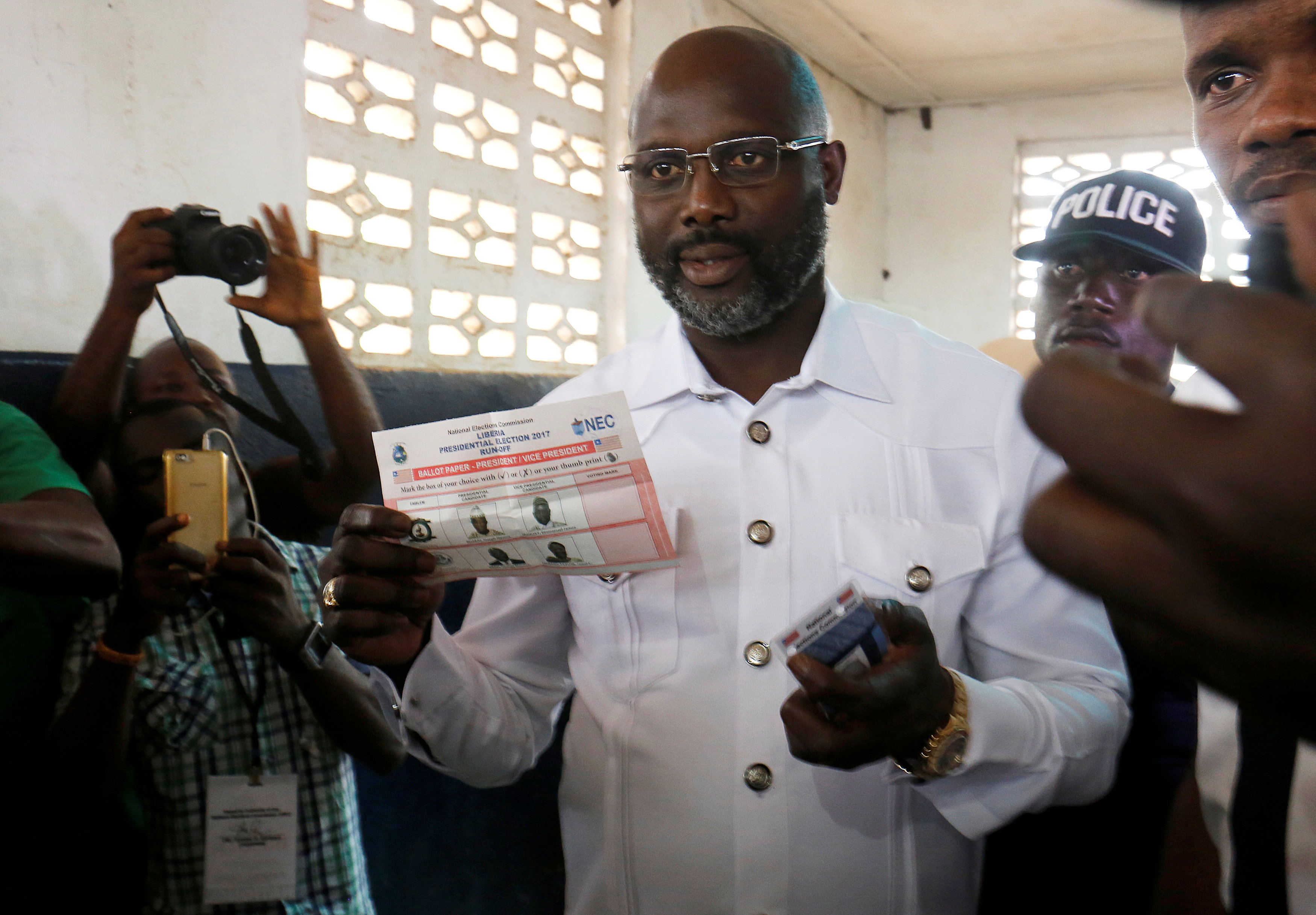 George Weah, former soccer player and presidential candidate of Congress for Democratic Change (CDC), prepares his ballot during presidential elections at a polling station in Monrovia, Liberia, December 26, 2017.