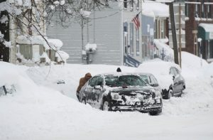 People help dig out a car from a parking spot after two days of record-breaking snowfall in Erie, Pennsylvania, U.S., December 27, 2017.