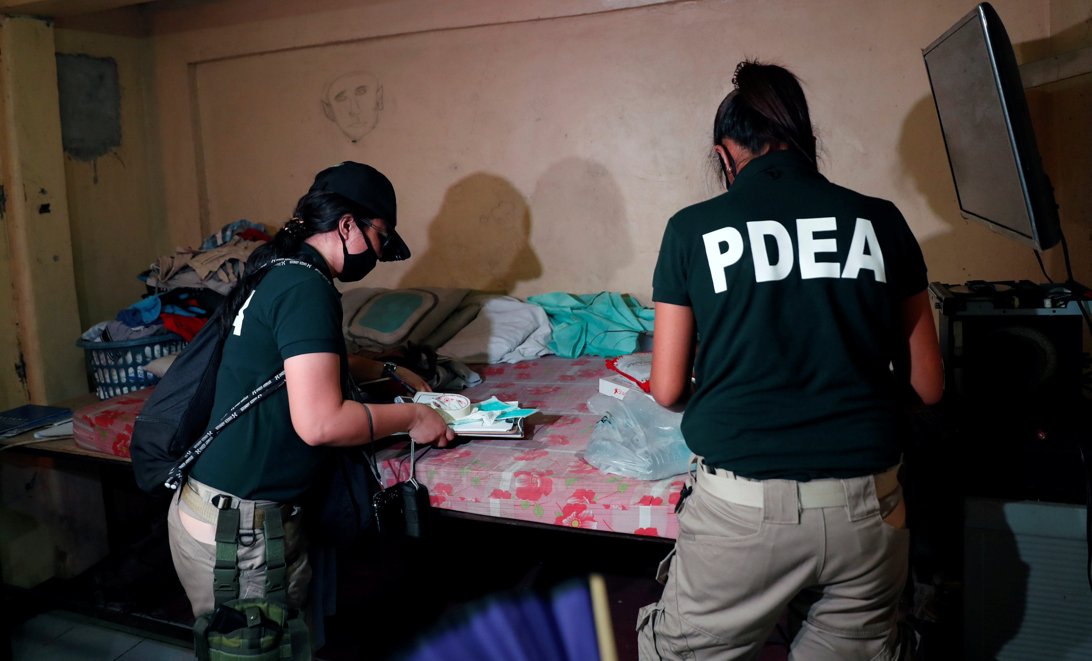 Agents of the Philippine Drugs Enforcement Agency (PDEA) search a house of a drug trafficker during a raid in Tondo, Manila, Philippines, December 10, 2017.