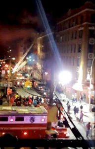 A crowd gathers as New York Fire Department personnel fight a fire in the Bronx borough of New York City, New York, in this still image taken from a December 28, 2017 social media video.